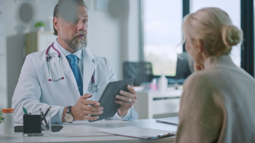 Family Medical Doctor Showing Mammography Test Results to a Senior Patient on a Tablet Computer in a Health Clinic. Friendly Assistant Explains Importance of Breast Cancer Prevention Screening. Royalty-Free Stock Footage #1059016568