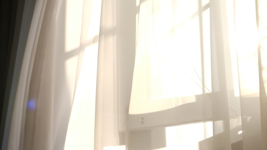 wind blows through the open window in the room. Waving white tulle near the window. sun's rays shine through the transparent tulle Royalty-Free Stock Footage #1059018158