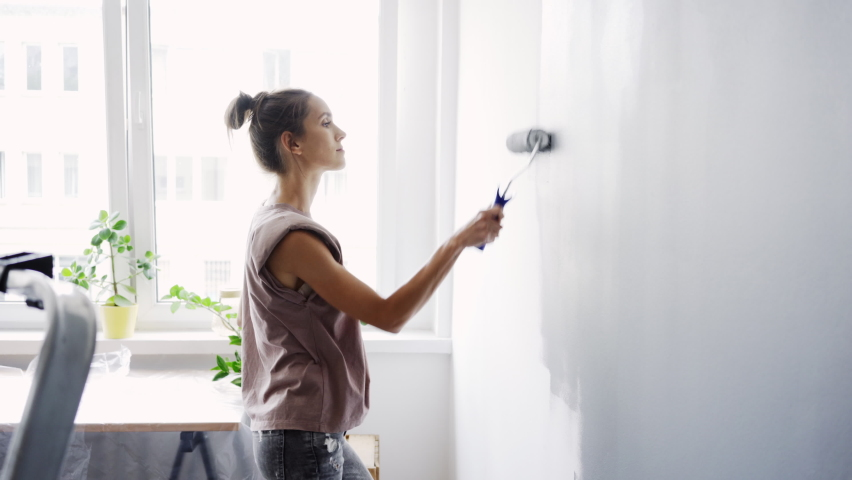Young woman painting wall in apartment