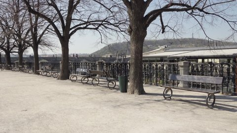 A deserted walkway with benches through a park without people during the coronavirus pandemic