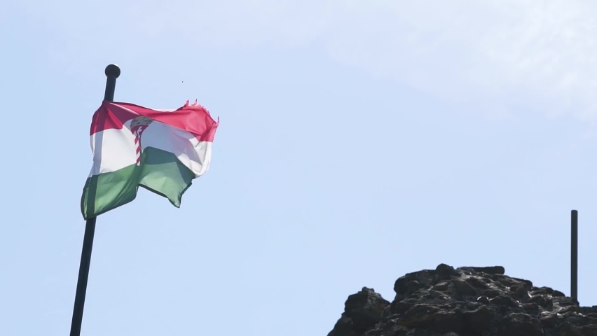 Hungarian national flag waving on top of the hill. Slow motion stock video. Focus on the flag. | Shutterstock HD Video #1059024389