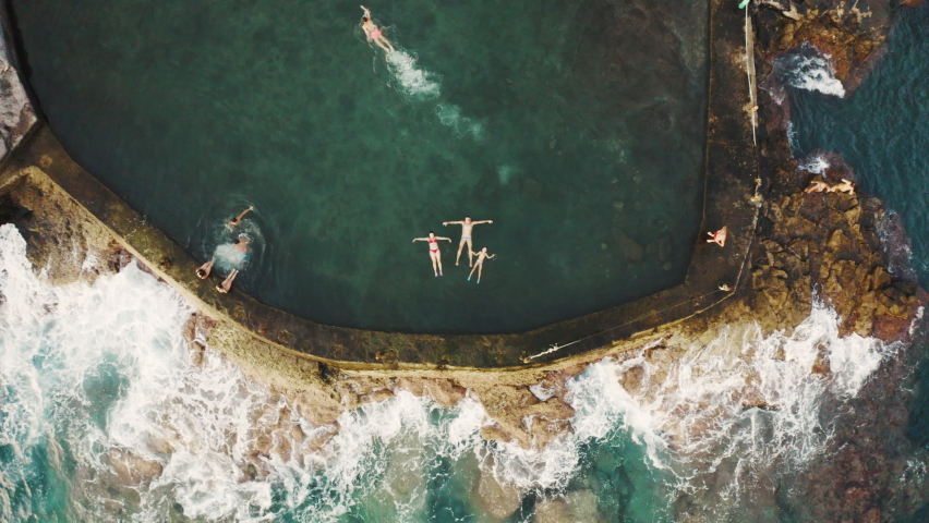 Aerial video of a family enjoying a natural pool in the Atlantic ocean of Tenerife, Canary Islands
