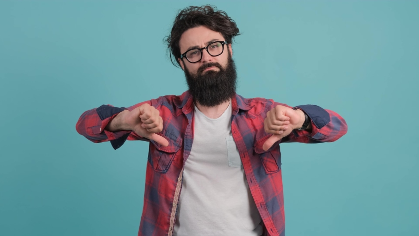 Young bearded man standing on turquoise background showing thumb down gesture at camera. | Shutterstock HD Video #1059028007