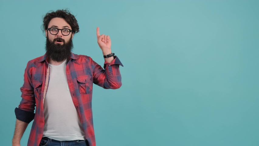 Handsome bearded man standing over turquoise background pointing finger up with successful idea. Exited and happy. | Shutterstock HD Video #1059028016