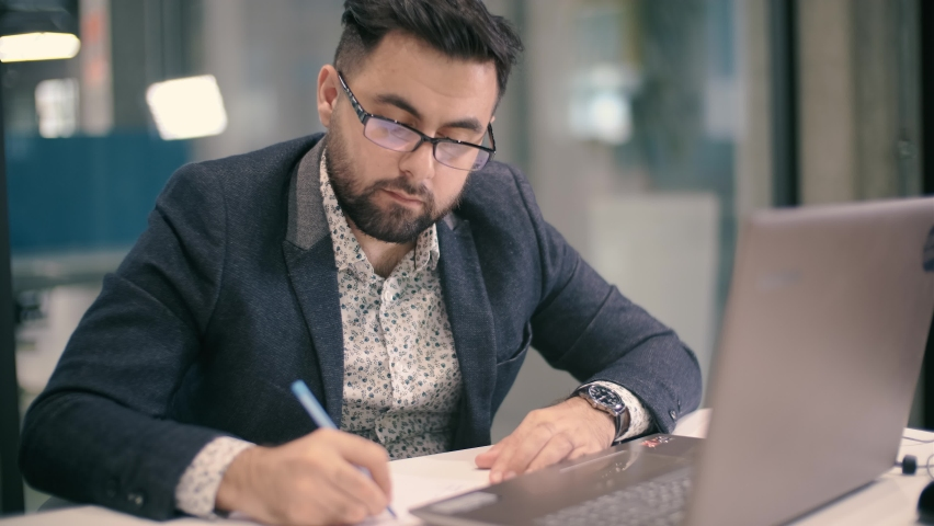 Young man watching an online lesson, making notes, looking at the computer screen while listening to her business coach. The girl is studying remotely. Royalty-Free Stock Footage #1059028307