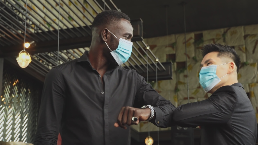 Handheld: African American black man and Asian friend wearing protective face mask elbow bump greeting for social distancing and new normal business etiquette to prevent Coronavirus infection Royalty-Free Stock Footage #1059034274