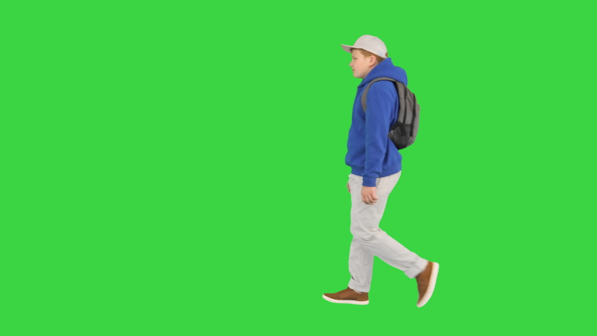 Young boy wearing a backpack walking to school on a Green Screen, Chroma Key.