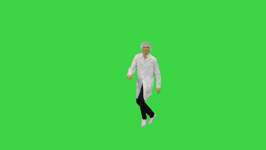 Young male doctor in white robe and protective cap doing backspin breakdance and looking at camera at the end on a Green Screen, Chroma Key.