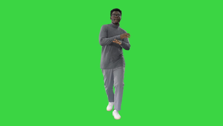 Young african american man in grey clothes and glasses grooving while walking on a Green Screen, Chroma Key.