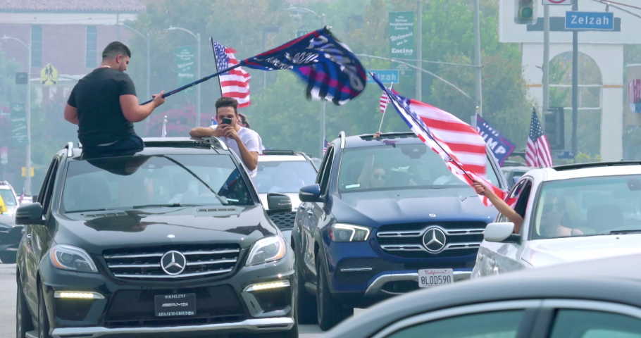 LOS ANGELES, CALIFORNIA, USA - SEPTEMBER 13, 2020: President Donald Trump supporters in cars with American flag driving in Los Angeles, California, 4K