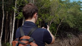 Adult Man Traveler with Backpack Makes Photo and Video on Smartphone of River and Green Mangrove Forest. Back View. Tourist Shooting Clip for Social Media Stories by Phone Standing near Creek in Woods