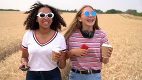 Slow motion video clip of pretty blonde girl and mixed race teenager young women wearing sunglasses drinking coffee and using their smart phones for social media