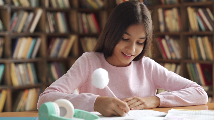 Smiling smart indian latin preteen school girl pupil studying at home sitting at desk. Happy cute hispanic kid primary school student writing in exercise book doing homework, learning at table.