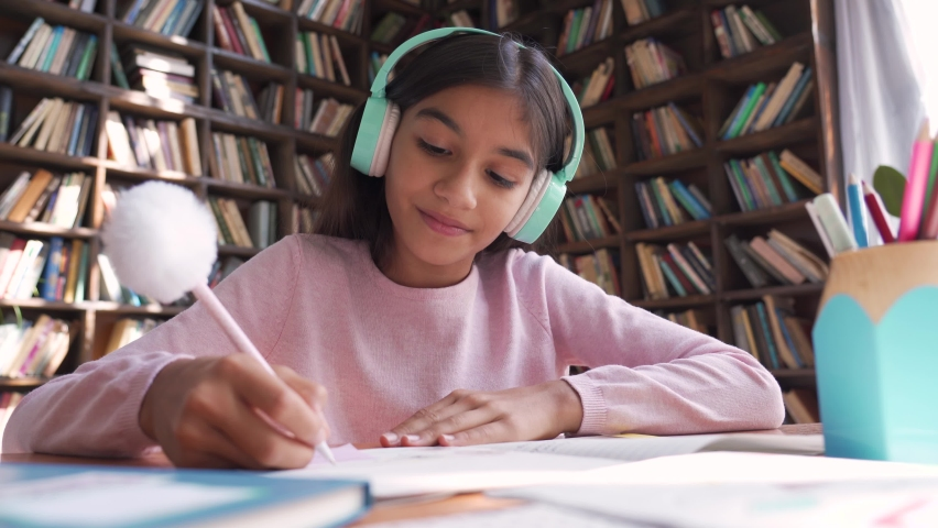 Indian latin preteen girl school kid child pupil wearing headphones distance learning online looking at web camera at virtual remote lesson class by video conference call at home, webcam view. Royalty-Free Stock Footage #1059048698