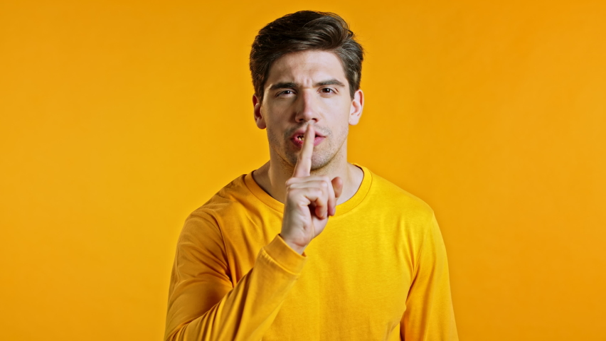 Handsome man holding finger on his lips over yellow background. Gesture of shhh, hush, secret, silence. Close up. | Shutterstock HD Video #1059048743