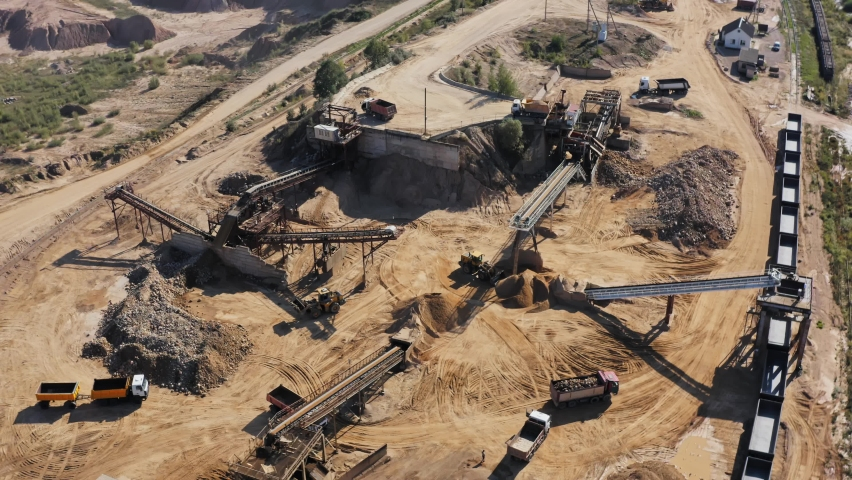 Aerial view of sand quarry, industrial extraction of sand for construction industry. Excavators and tractors load crushed stone and rock into dump trucks. Mining truck transporting sand