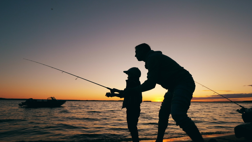 A man is helping his son with fishing at sunset