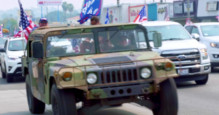 LOS ANGELES, CALIFORNIA, USA - SEPTEMBER 13, 2020: President Donald Trump supporters in military Humvee car with American and Israel flag driving in Los Angeles, California, 4K