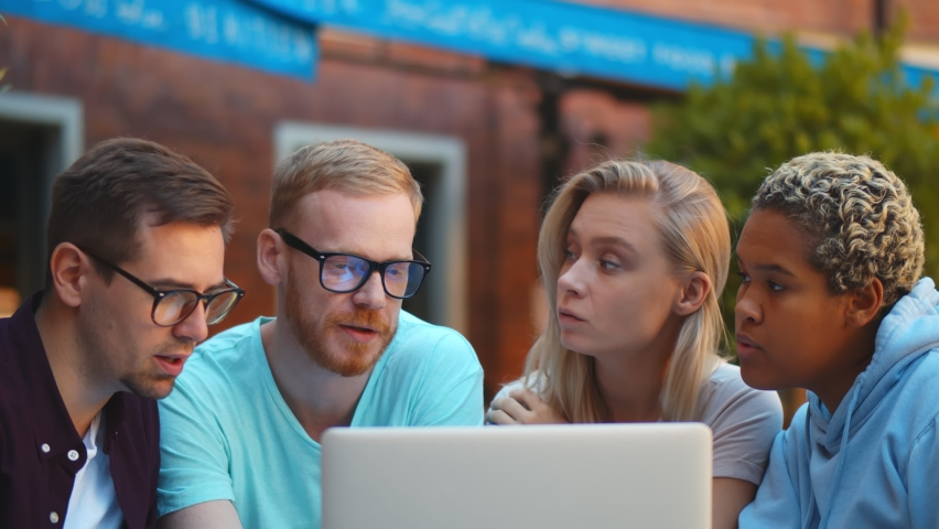 Interracial Students Friends Using Laptop Outdoors, Checking Results Of Their Exams. Diverse creative team working on computer sitting outdoors during coffee break Royalty-Free Stock Footage #1059057737
