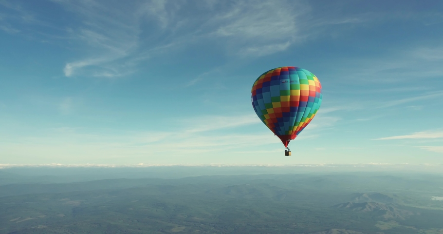 Colorful hot air balloon epic flying above mountain over the fog at sunrise with beautiful sky background - High altitude aerial drone wide view | Shutterstock HD Video #1059058211