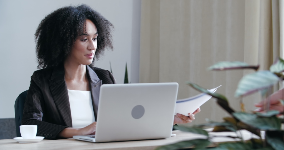 Busy woman office worker sits at desk in company, works surfing Internet, uses laptop to process data information, analyze analytics, work on project, gets picks up paper documents report for approval Royalty-Free Stock Footage #1059058598