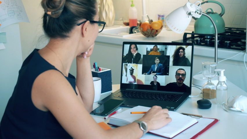 A lady is greeting her colleagues during a video conference call. Meeting online, remote work using videocall. Royalty-Free Stock Footage #1059061616