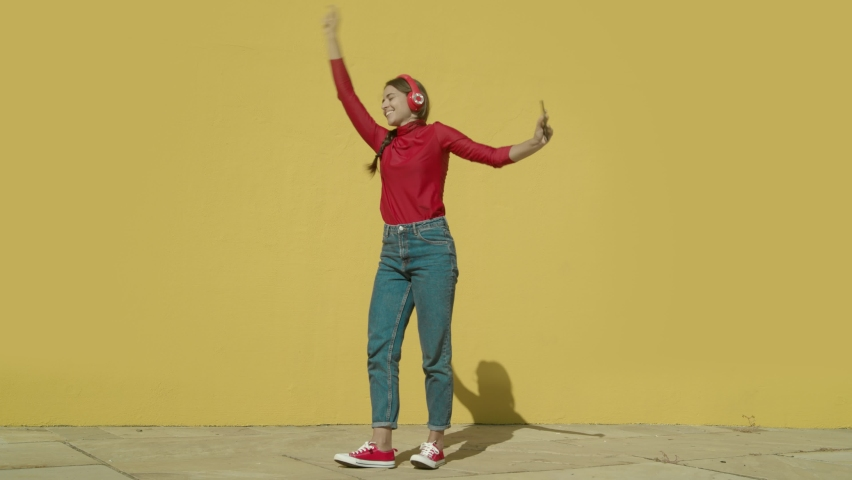Young Happy Latin Woman wearing red shirt and jeans and red converse shoes starts dancing with a yellow background wall on a sunny day wide-angle shot