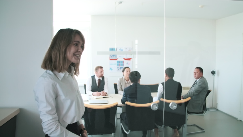 Young office secretary welcoming mature businessman and opening board room door for him to enter | Shutterstock HD Video #1059071177