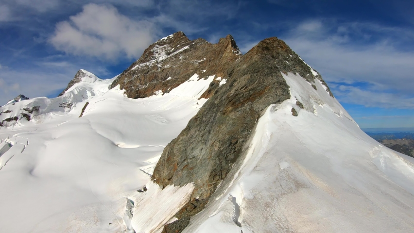 FPV drone view, rising over rocky, alpine peaks, at the top of Europe, Jungfraujoch, on a sunny, summer day, in the Bernese Alps of Switzerland | Shutterstock HD Video #1059071507