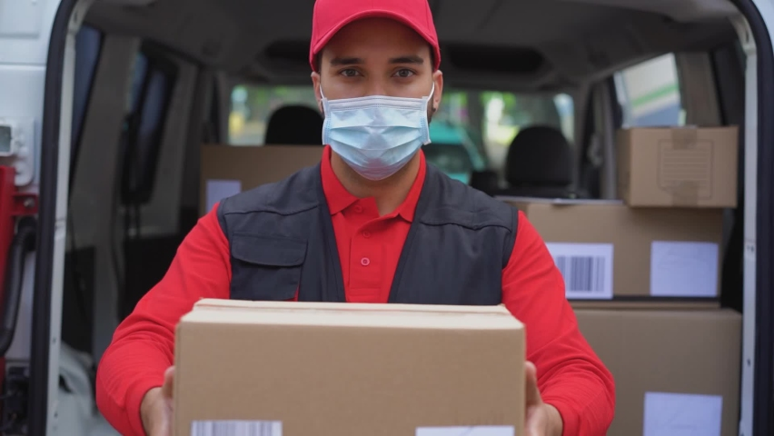 Young delivery man holding package in his hands while wearing face mask for coronavirus spread prevention - Slow Motion  | Shutterstock HD Video #1059072605