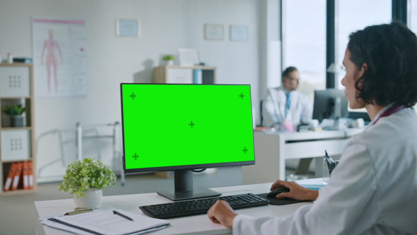 Female Medical Doctor is Working on a Computer with Green Screen Mock Up Display in a Health Clinic. Assistant in White Lab Coat is Reading Medical History Behind a Desk in Hospital Office. | Shutterstock HD Video #1059073805