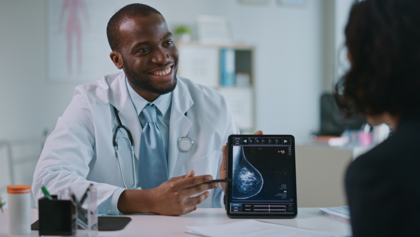 Young Black Medical Doctor Showing Mammography Test Results to a Patient on a Tablet Computer in a Health Clinic. Friendly Assistant Explains Importance of Breast Cancer Prevention Screening.   Shutterstock HD Video #1059073913