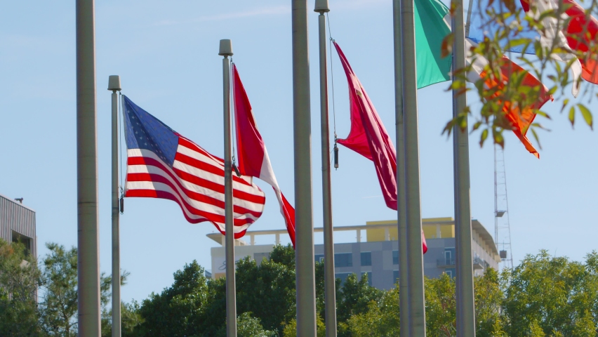 A backlit American flag, Canadian flag, Chinese flag, Irish flag, and French flags blowing in the wind with a building in the background. | Shutterstock HD Video #1059085505