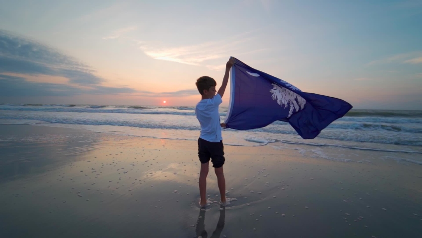 Boy standing on Myrtle Beach at sunrise waving South Carolina Flag. . High quality FullHD footage