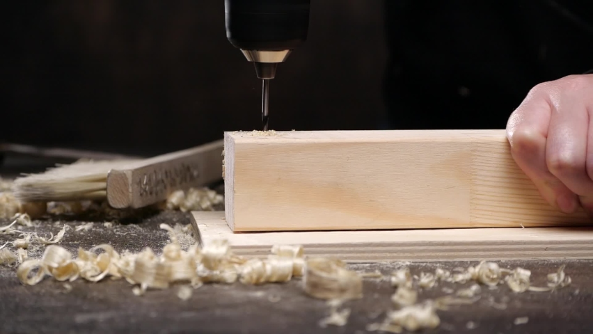 Crop carpenter using electric drill to make hole in lumber plank on workbench in joinery   Shutterstock HD Video #1059088964