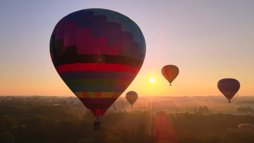 Aerial drone view of colorful hot air balloon flying over green park and river in small european city at summer sunrise, Kiev region, Ukraine | Shutterstock HD Video #1059090299