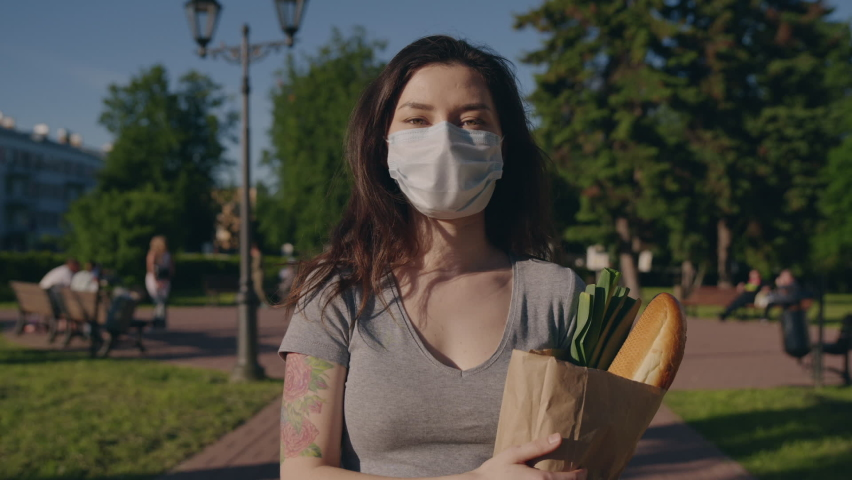 Pandemic shopping. Young woman in protective mask and gloves carries bag with products from store to home. Social distance for prevent outbreak. Another life after quarantine. Covid effect concept. | Shutterstock HD Video #1059092930
