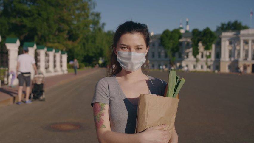 Pandemic shopping. Young woman in protective mask and gloves carries bag with products from store to home. Social distance for prevent outbreak. Another life after quarantine. 6K Downscale | Shutterstock HD Video #1059092957