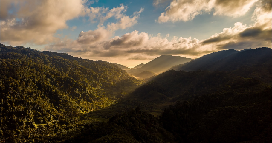 Aerial drone hyperlapse timelapse of beautiful tropical valley between mountains. The first rays of the rising sun break through the clouds and clouds. The last rays of the sunset hit the tree crowns. | Shutterstock HD Video #1059094115