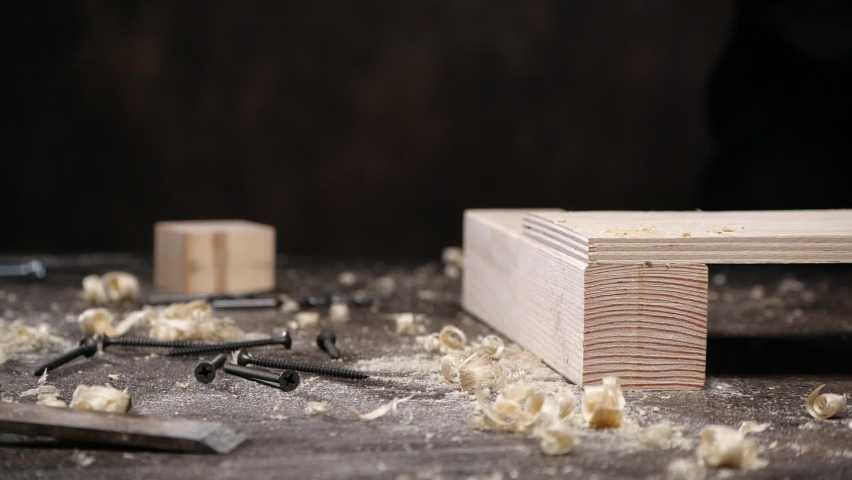 Unrecognizable artisan removing wooden dust from plank with brush on messy workbench with chips and nails   Shutterstock HD Video #1059094370