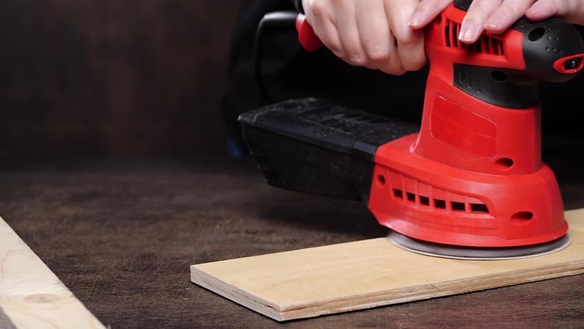 Unrecognizable carpenter using eccentric polishing machine on lumber plank on workbench in workshop   Shutterstock HD Video #1059094376