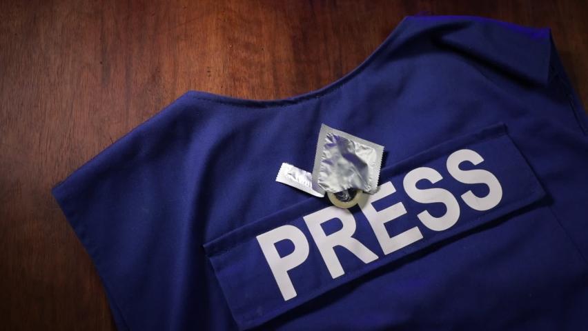 Media Journalism fake news concept. Blue journalist (press) vest in dark with backlight and fog. Dirty money on journalist vest. Selective focus   Shutterstock HD Video #1059094430