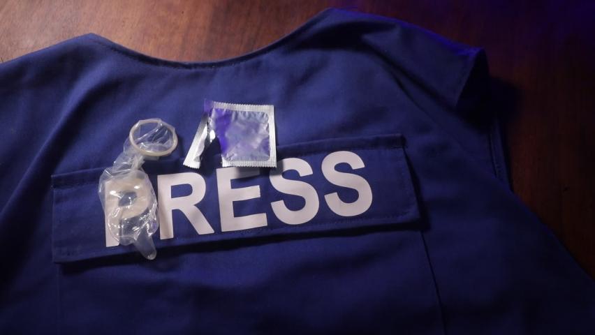 Media Journalism fake news concept. Blue journalist (press) vest in dark with backlight and fog. Dirty money on journalist vest. Selective focus   Shutterstock HD Video #1059094436