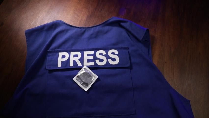 Media Journalism fake news concept. Blue journalist (press) vest in dark with backlight and fog. Dirty money on journalist vest. Selective focus   Shutterstock HD Video #1059094439