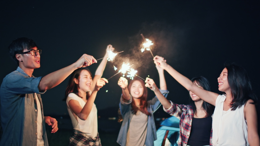 Group of young Asian college student friends lit light sparkler, sing and dance together at beach camping tent. Party people, love friendship relationship, or outdoor camping activity concept Royalty-Free Stock Footage #1059096788