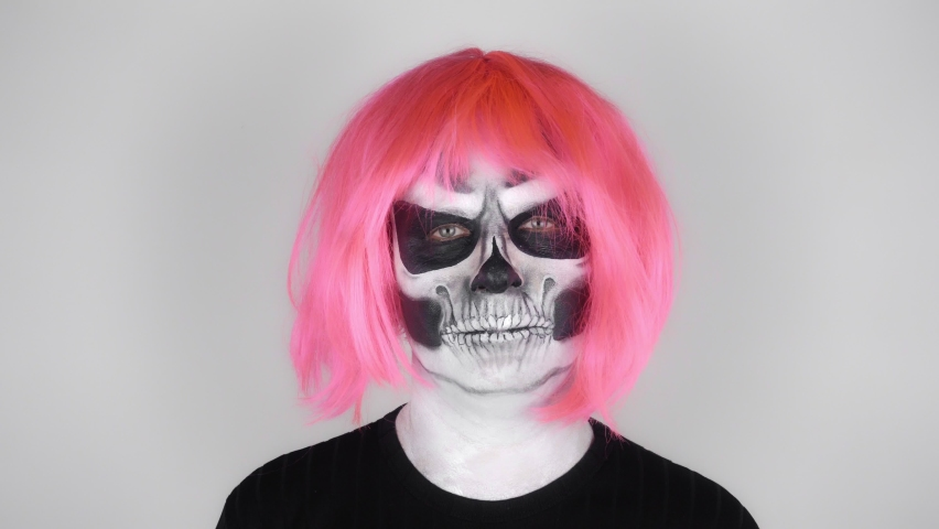 Funny man in halloween skeleton make-up in pink wig takes off his wig and uses it as a fan. Shooting in the studio. Gray background | Shutterstock HD Video #1059096863
