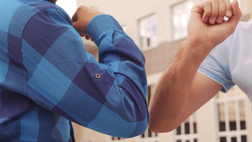 two businessmen touch elbows social distance. bump avoid greeting. coronavirus pandemic concept. two men meeting greet each other at distance observing social distance. bump avoid lifestyle greeting Royalty-Free Stock Footage #1059098141