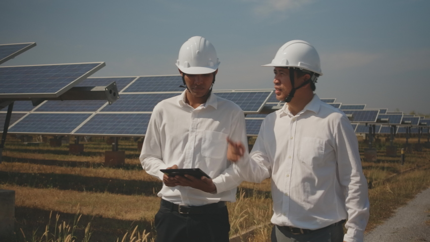 Technician and investor walking in Solar cell Farm through field of solar panels checking the panels at solar energy installation.Solar cells will be an important renewable energy of the future. | Shutterstock HD Video #1059107147