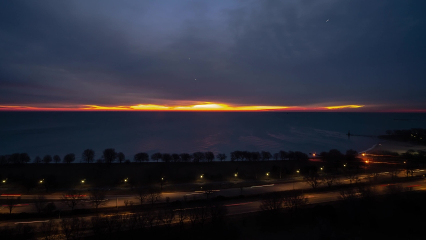 Chicago, IL - March 11th, 2019: The sun rises over the horizon peeping  between the water of Lake Michigan and the cloudy sky above as traffic drives by on Lake Shore Drive as night turns to day.