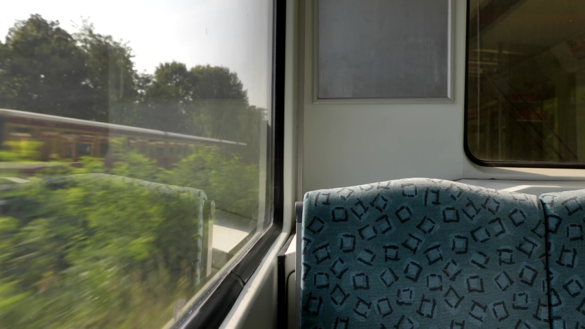 Interior view at train's empty window seat window move through countryside in Berlin, Germany. Window side view during commute and travel by Train.  Royalty-Free Stock Footage #1059121022